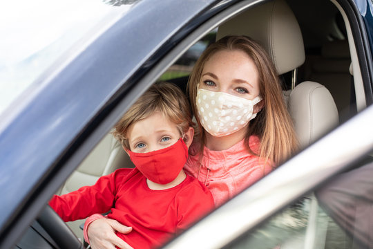 Little boy with her mom in a car wearing face masks to prevent spread of coronavirus Covid-19 virus pandemic.