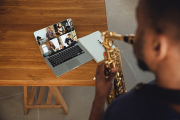 African-american musician playing saxophone during online concert at home isolated and quarantined. Using camera, laptop, streaming, recording courses. Concept of art, support, music, hobby, education Fotobehang
