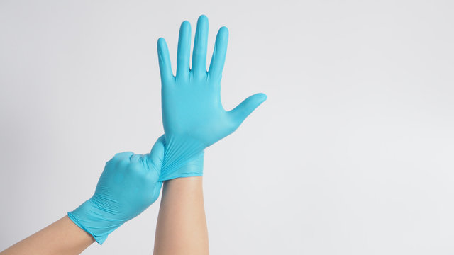 Hand is pulling blue latex gloves on white background.