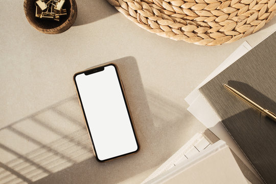 Flatlay of blank screen smartphone, notebooks, clips in wooden bowl, straw stand on beige concrete background. Home office desk workspace. Business, work template. Flat lay, top view.