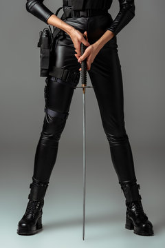 cropped view of futuristic african american woman with sword on grey