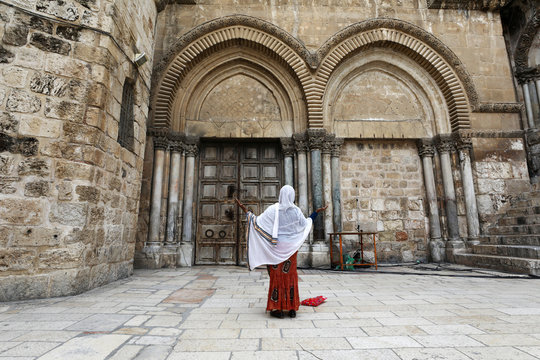 A woman prays next to the closed doors of the Church of the Holy Sepulchre on the day that Greek Orthodox church authorities celebrate Good Friday amid the coronavirus disease (COVID-19) outbreak, in Jerusalem's Old City