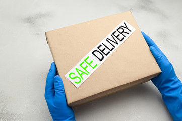 Safe delivery of packages at home during coronavirus pandemic. Courier's hands in blue medical gloves are holding a cardboard box on a light background. Online shopping, stay home concept. Top view