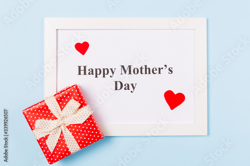 White picture frame with text Happy Mother's Day , gift box and red heart on light blue background . Happy Mother's Day concept.