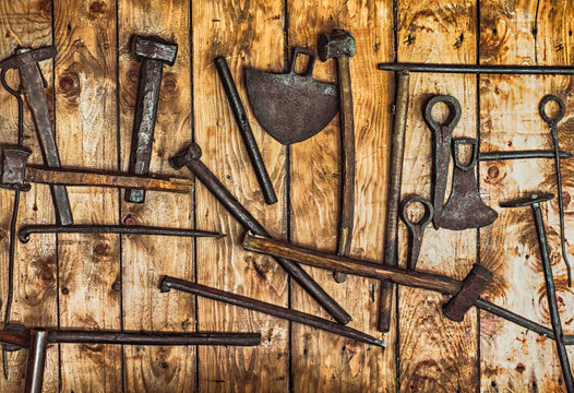 rudimentary gold mining tools hanging on a wall of planks