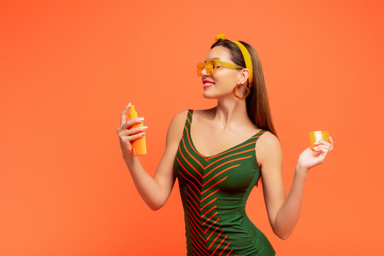 Woman smiling and applying sunscreen isolated on orange