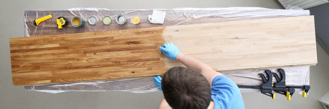 Woodworker varnishing surface