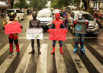 Volunteers wearing superhero costumes carry banners for a campaign against the spread of the coronavirus disease (COVID-19) in Makassar