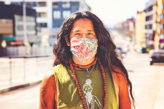 Man with long hair wearing protective face mask in the city