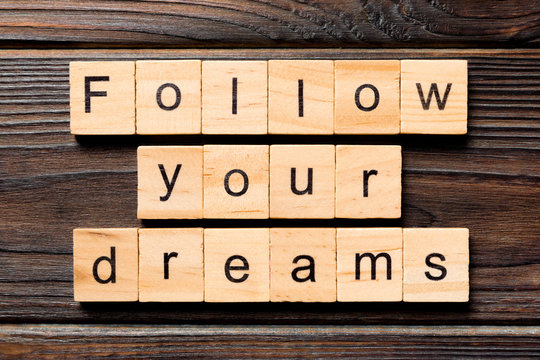 Follow your dreams word written on wood block. Follow your dreams text on wooden table for your desing, Top view concept