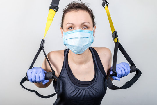 Young attractive woman training with trx fitness straps and mask.