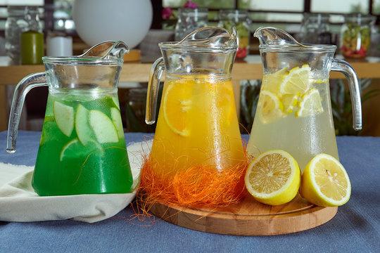three varieties of summer lemonade in jugs on a blue tablecloth closeup