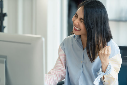 Successful excited working woman raised arm with happy at work in front of computer monitor.