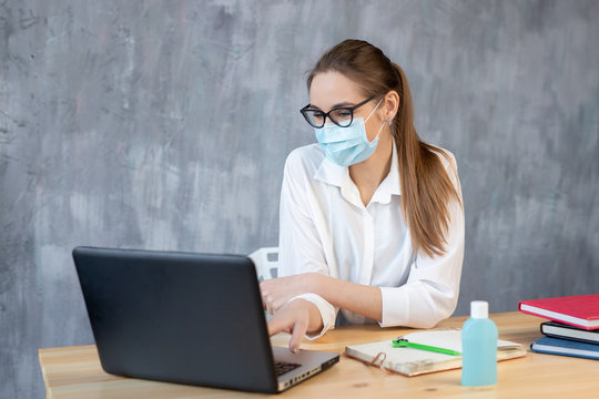Coronavirus. Young business woman working from home wearing protective mask. Business woman in quarantine