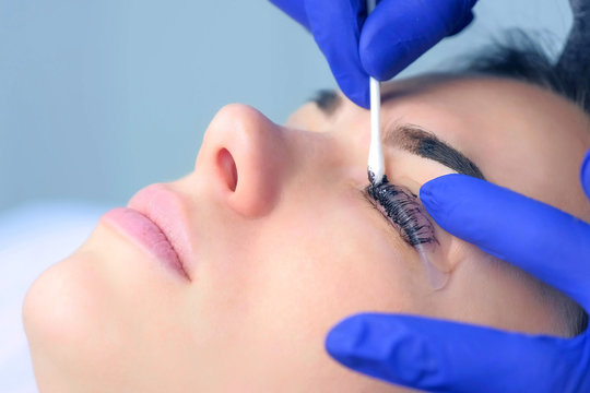 Cosmetologist wiping paint from lashes and brows of woman, side view. Beautician ending lash lifting laminating, painting lashes and eyebrows procedure in cosmetology clinic. Beauty procedure.