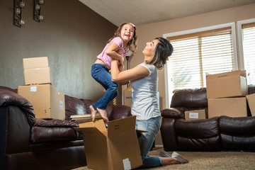 A Hispanic mother holds daughter up in a new House