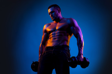 Fitness Model showing his perfect body. Muscular guy doing exercises with dumbbell over neon black blue background.