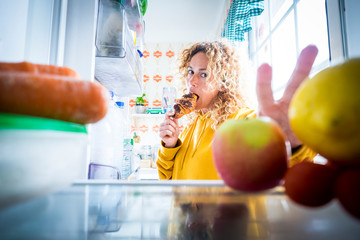 Alternaive inside view of Beautiful hungry adult woman eat tasty croissant with chocolate and open the fridge to take off some food -  concept of coronavirus covid-19 lockdown quarantine people Fototapete