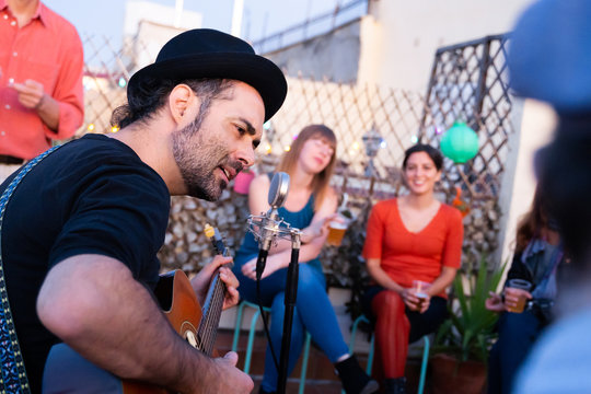 Lead singer of a rock band singing for audience on a rooftop. Portrait of a hipster male musician playing on an intimate concert. Man performing an acoustic guitar concert. Music live concerts concept