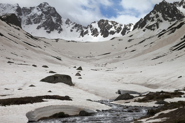 Fototapete - River with snow bridges in high snowy mountains at spring evening