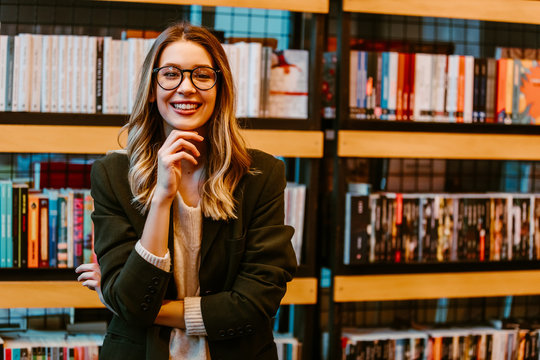 Portrait of pretty smiling woman in casual wear standing at book store. Young woman with glasses posing in front of camera.