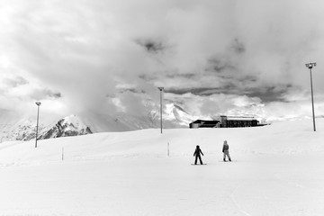 Fototapete - Snowy ski slope with silhouette of snowboarders