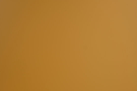 Light brown background. Dark yellow abstract background. Simple background with soft gradient.