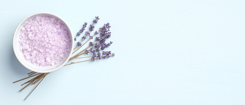 Lavender salt with flowers on blue background. Natural organic SPA product, skin care and body treatment concept. Flat lay, top view, copy space
