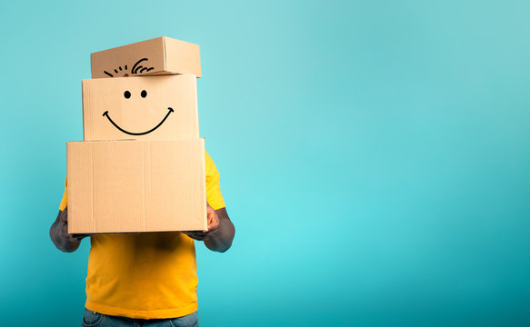 Man is hidden by too many received packages. Cyan background