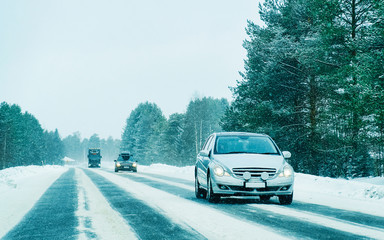 Wall Murals Road in forest Car at the road in snowy winter Lapland reflex