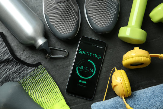 Smartphone with step counter app and fitness accessories on black background, flat lay