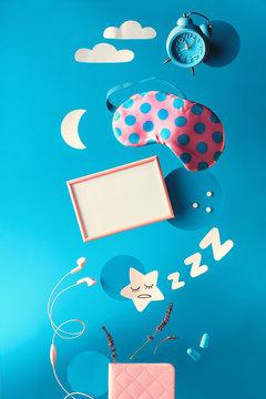 "Healthy sleep creative concept, text ""Sleep optimization"" on lightbox. Flying or levitating sleeping mask, alarm clock, earphones, earplugs, pills. Paper moon star, clouds on blue mint background."