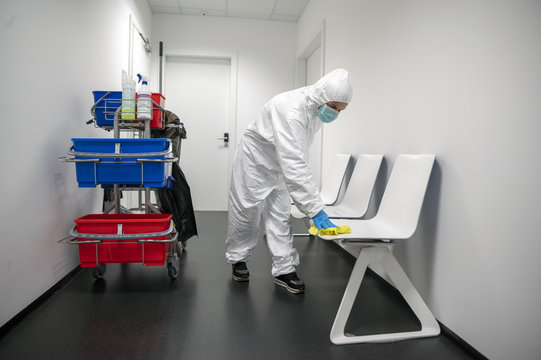 Alert Corona Virus or Covid-19. Cleaner with full protective suit, masks and gloves cleans, disinfects and sanitizes the waiting room of a hospital, clinic or ublic place. Cleaning of chairs.