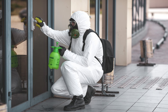 Quarantine, coronavirus infection. A man in protective equipment disinfects with a sprayer in the city. Cleaning and Disinfection at the street. Protective suit and mask. Epidemic.