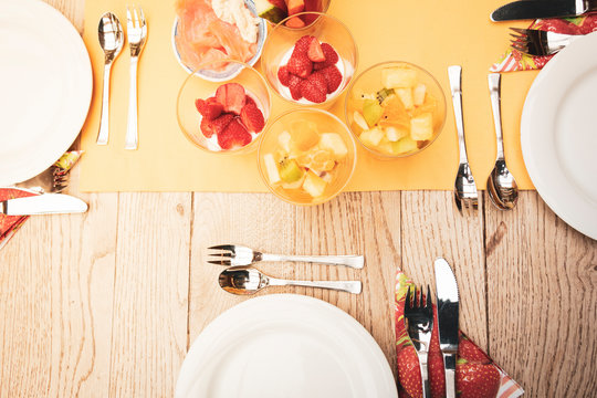 real set breakfast table with small glass bowls full of fruits and fish, yellow tablecloth, silver cutlery, white plates on wooden table