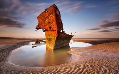 Tuinposter Schipbreuk An old shipwreck boat abandoned stand on beach or Shipwrecked off the coast of Ireland