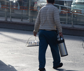 Fototapeta Man selling tea in thermos on the street. In his other hand, he carries glass glasses on a handle tray. obraz