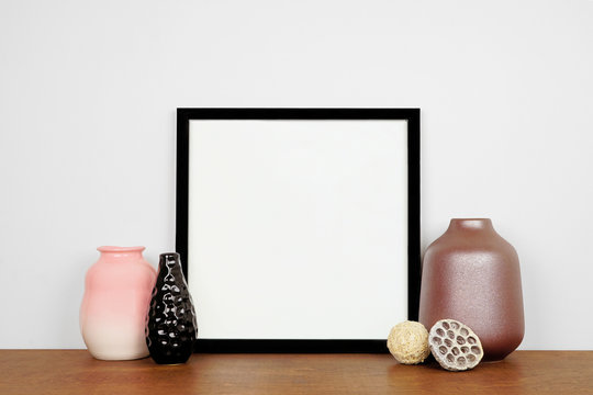 Mock up black square frame with vase home decor. Wooden shelf against a white wall. Copy space.