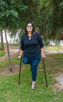 Young beautiful amputee woman walking with crutches
