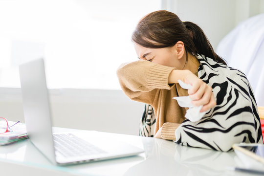 Asian woman sneezing on hinge joints arm at home.Work at home.Coronavirus COVID-19 reducing of risk of spreading the infection by covering nose and mouth when coughing and sneezing with tissue.
