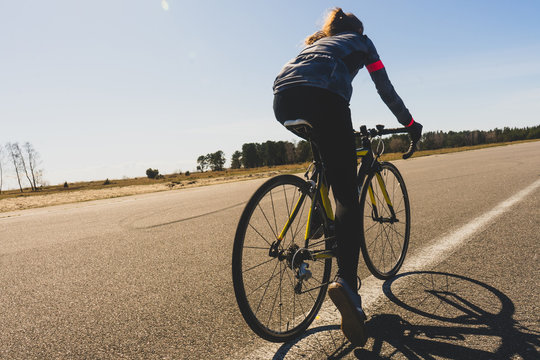 Blurred image of a woman cyclist on a sunny summer day. Healthy lifestyle and sports theme. Biker in motion