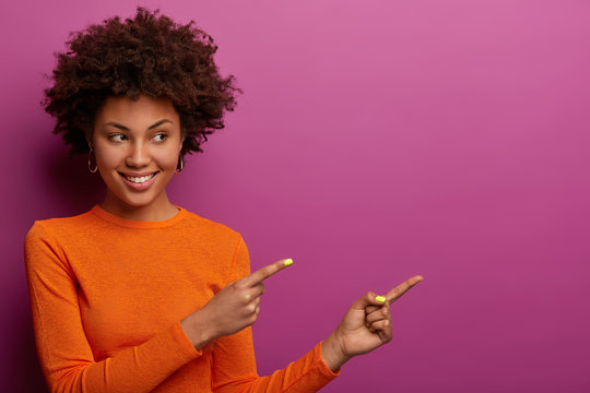 Good looking woman points right at copy space blank for your promotion, gives advice to click link, dressed in orange jumper, smiles pleasantly, isolated on bright purple wall recommends order product