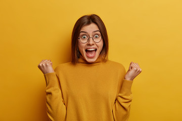 Emotional cheerful woman celebrates amazing news and win, clenches fists from delight, celebrates...