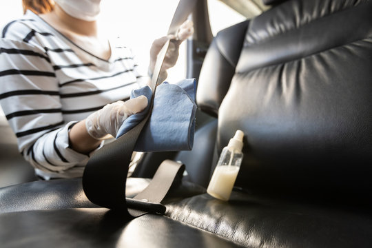 Woman wearing glove,girl with alcohol antiseptic,spray bottle disinfecting,cleaning on seat belt in car,protection during Coronavirus pandemic,Covid-19,wipe to clean the surfaces with disinfectant