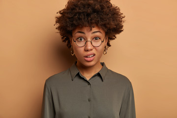Discontent young African American woman expresses scorn and disbelief, smirks face with dissatisfaction, wears transparent optical glasses and shirt, poses indoor against brown studio background