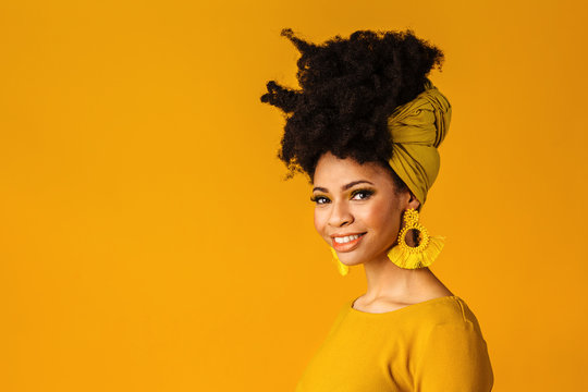 Portrait of a smiling young woman with big yellow tassel beaded earrings and afro hair wrapped with head wrap scarf