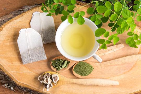Moringa tea, leaves, seeds, powder on a wooden background - Moringa oleifera