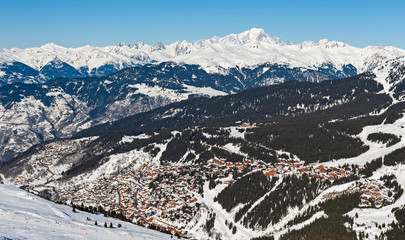 Wall Mural - Panoramic view down snow covered valley in alpine mountain range with ski resort