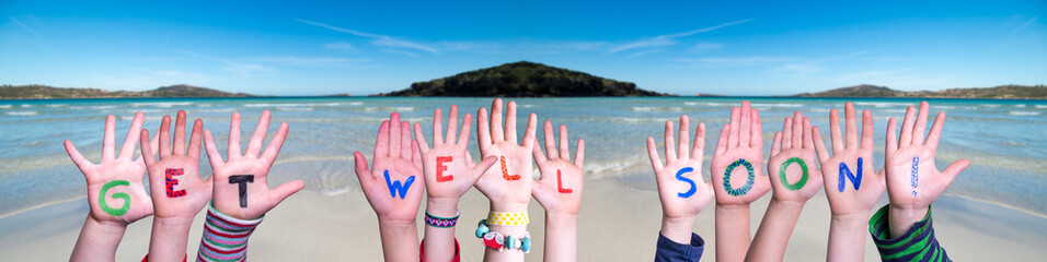 Children Hands Building Colorful English Word Get Well Soon. Ocean And Beach As Background