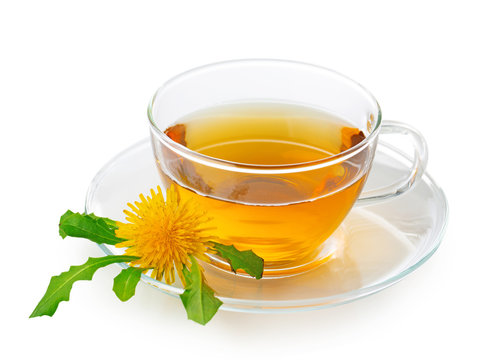 Dandelion tea in a transparent cup with dandelion flower and leaves